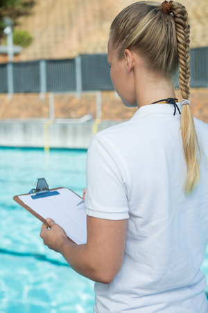 Rear view of female coach writing on clipboard at poolside