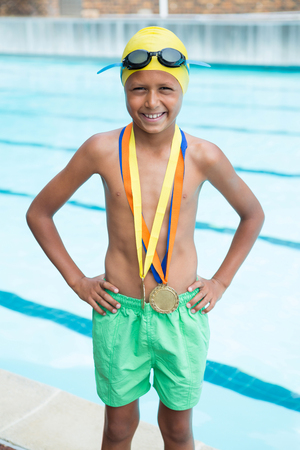 Portrait of smiling boy with gold medals around his neck standing near poolside Stock Photo