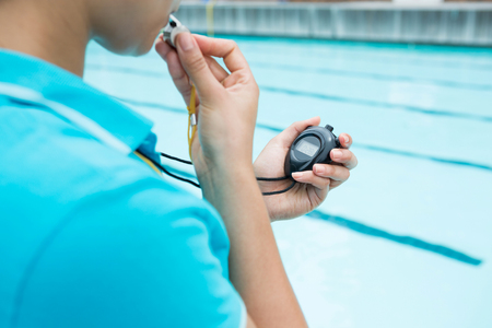 Female coach blowing whistle and looking at stopwatch near poolside Фото со стока