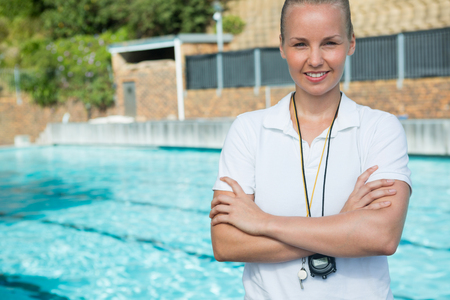Portrait of female trainer standing with arms crossed at poolside Stock Photo