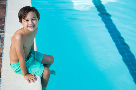 Portrait of smiling boy sitting at poolside
