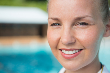 Portrait of smiling female coach standing near poolside at the leisure center
