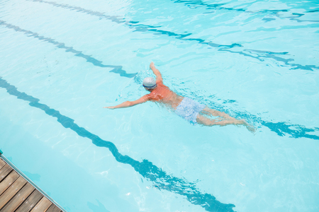 Rear view of senior man swimming in pool Stock Photo