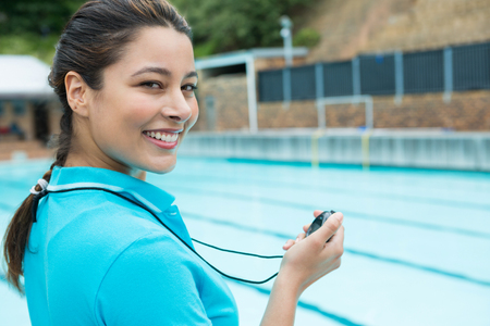 Portrait of smiling swim coach holding stopwatch near poolside Stock Photo