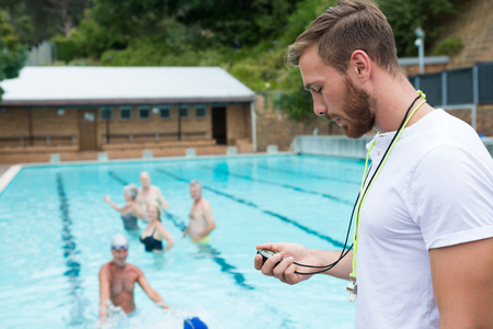 Swim coach looking at stopwatch near poolside at the leisure center