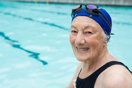 Portrait of smiling senior woman sitting at poolside