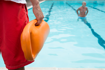 Mid section of lifeguard holding rescue buoy at poolside Foto de archivo