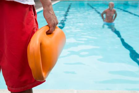 Mittlerer Abschnitt von Rettungsschwimmer hält Rettungsboje am Pool Standard-Bild - 75906040