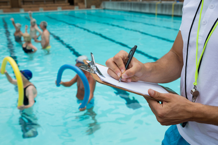 Mid section of swim coach writing on clipboard near poolside Stock Photo
