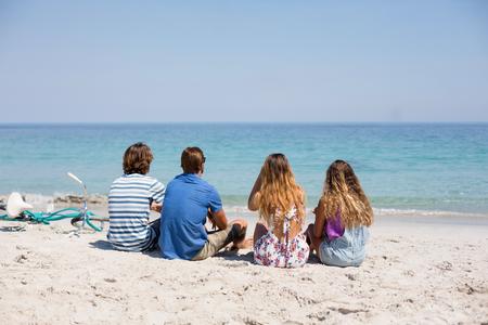 comunicacion oral: Vista trasera de amigos sentado en la playa en la playa durante el día soleado