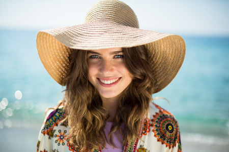 Close up portrait of happy young woman wearing sun hat against sea
