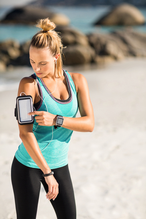 comunicacion oral: Young woman using smartphone on armband while listening music at beach