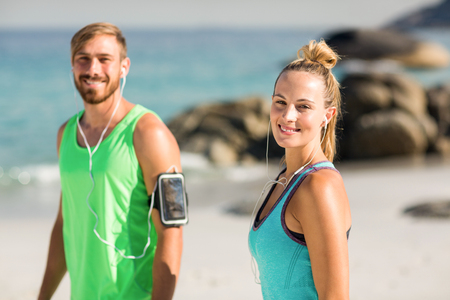 comunicacion oral: Portrait of happy couple in sports clothing standing at beach