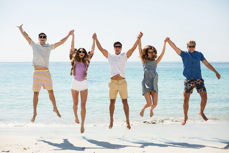 Happy friends jumping with arms raised at beach during sunny day