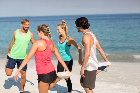 comunicacion oral: Amigos haciendo ejercicio en la playa en un día soleado