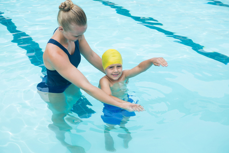 Female instructor training young boy in pool at leisure center