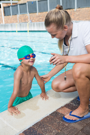 Female trainer showing stopwatch to boy at poolside