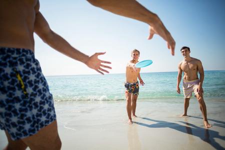 Hemdlose männliche Freunde, die Frisbee auf Ufer am Strand spielen Standard-Bild - 75907371