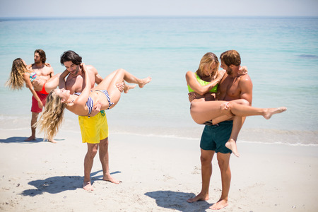 Men lifting women while standing on shore at beach during sunny day