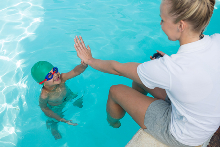 Female trainer giving high five to boy at poolside