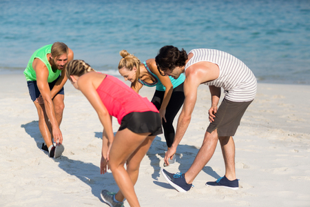 Male and female friends exercising on shore at beach Stock Photo