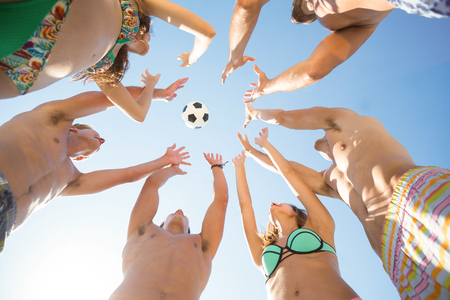Low angle view of friends throwing soccer ball in mid air Stock Photo