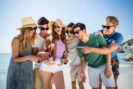 comunicacion oral: Cheerful friends looking in smartphone while standing at beach on sunny day Foto de archivo