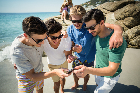 comunicacion oral: Cheerful male friends looking in smartphone while standing at beach