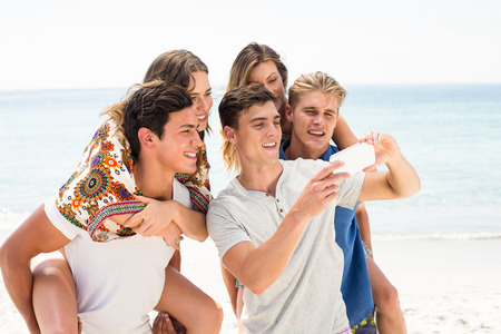 Happy friends looking in mobile phone at beach on sunny day