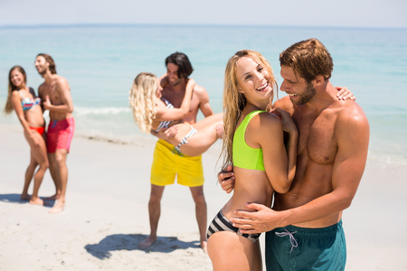 comunicacion oral: Side view of smiling young couple embracing at beach on sunny day Foto de archivo