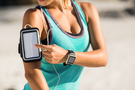 Midsection of woman using smartphone on armband at beach Stock Photo