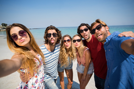 Cheerful friends making face while standing on shore at beach