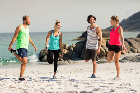 comunicacion oral: Full length of friends smiling while exercising at beach