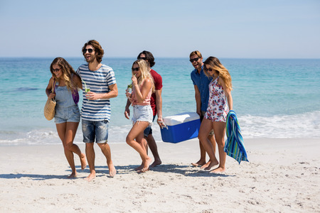 Full length of friends walking on shore at beach during sunny day