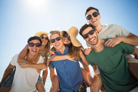 comunicacion oral: Smiling men piggybacking friends against sky on sunny day