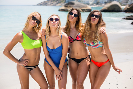 comunicacion oral: Young female friends in bikinis puckering while standing at beach on sunny day