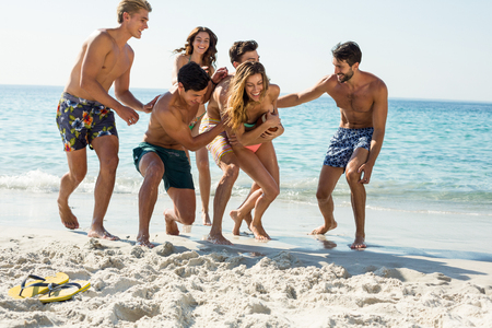 Full length of happy friends playing on shore at beach Stock Photo