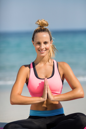 Close-up portrait of young woman meditating while sitting on shore at beach