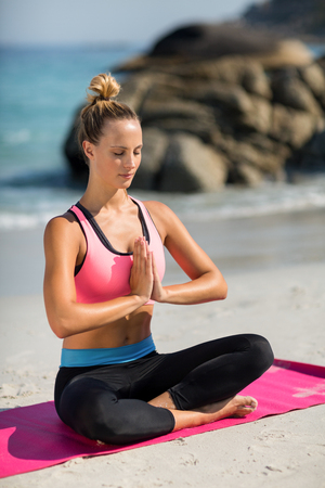 Full length of beautiful woman meditating while sitting at beach