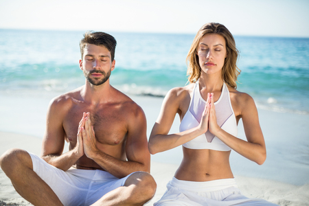 Young couple meditating while sitting on shore at beach Stock Photo