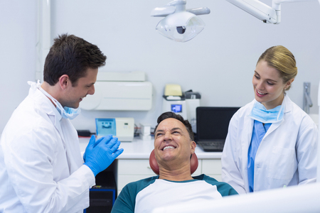 Dentists interacting with a male patient in clinic Stock Photo