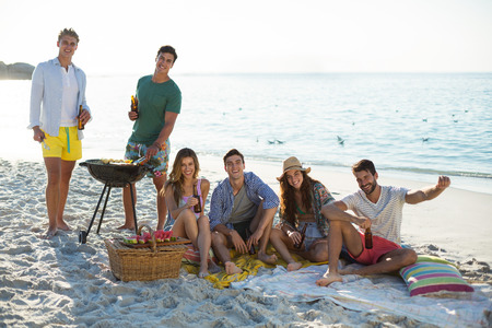 Portrait of smiling friends having drinks by barbecue at beach