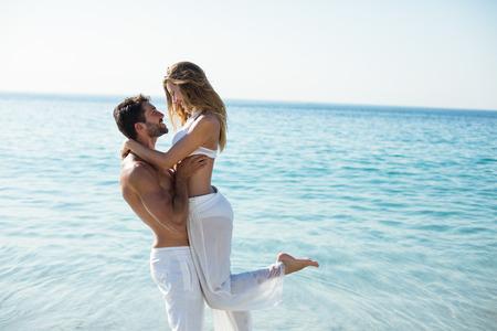 해변에 서있는 동안 여자 친구를 운반하는 남자의 측면보기