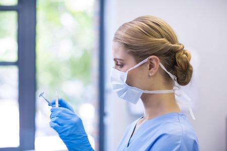 Female nurse holding dental tools in clinic Stock Photo