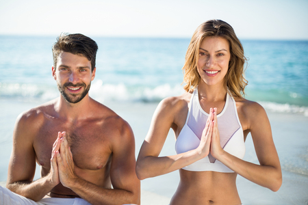 Close-up portrait of young couple meditating while sitting on shore at beach Stock Photo