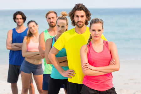 Portrait of friends in sports clothing standing at beach