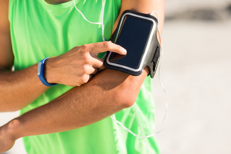 Midsection of man using phone while listening to music at beach