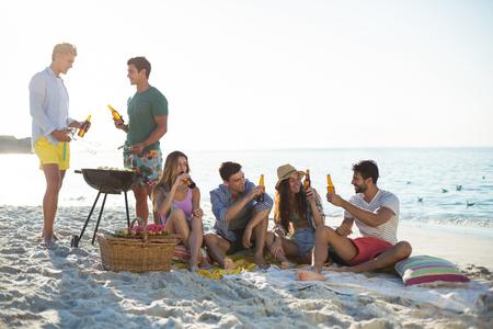 Glückliche Freunde, die Getränke durch Grill am Strand gegen Himmel haben