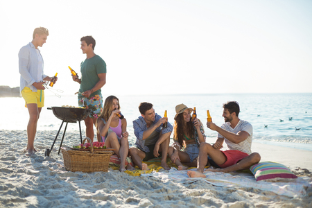 Happy friends having drinks by barbecue at beach against sky Stok Fotoğraf - 75909557