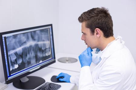 Dottore attento che esamina il rapporto di raggi x sul calcolatore in clinica Archivio Fotografico
